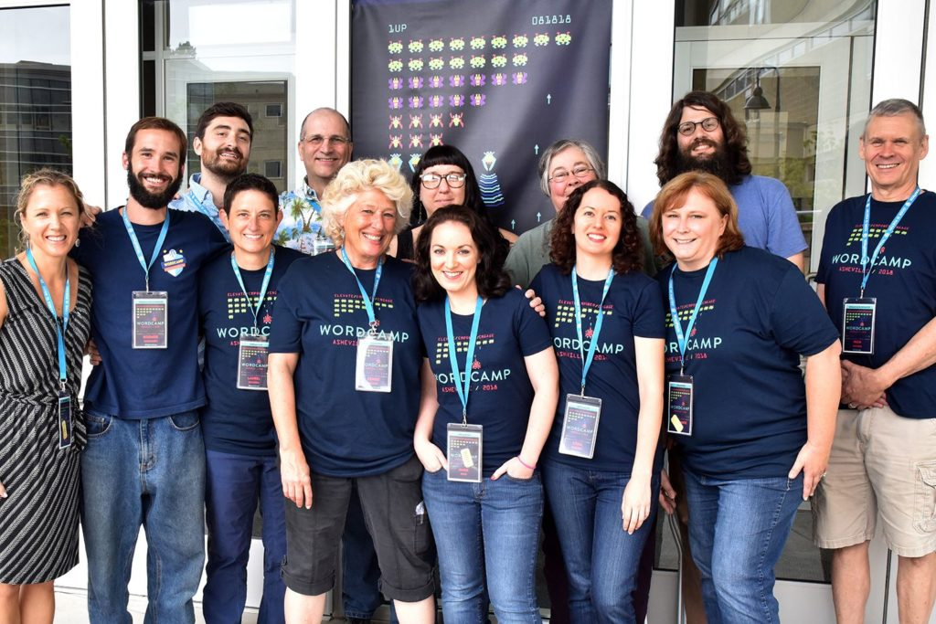 Group of WordCamp organizers stand smiling in front of 2018 banner