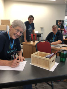 Female organizers smile at camera at registration