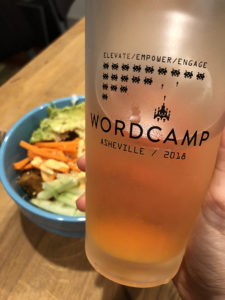 Frosted glass of beer with WordCamp Asheville logo printed on it