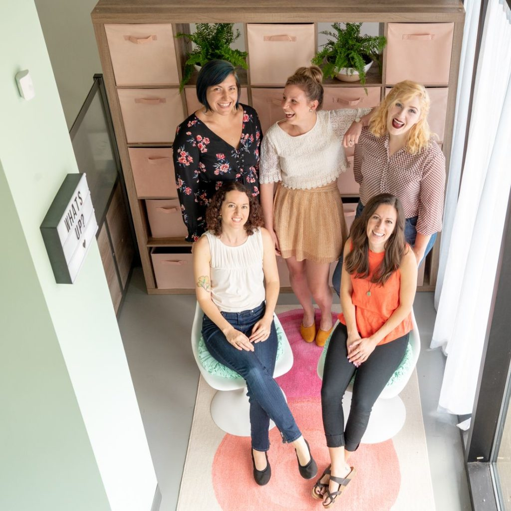 Group of young women sit smiling together in a modern chic office
