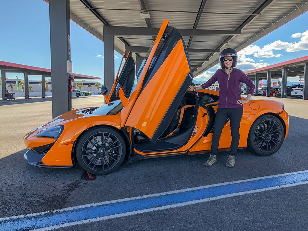 Lydia standing next to an orange McLaren 570s sports car